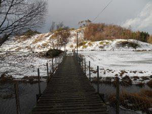 Broa til Øyno. Øykollen ligger rett bak det hvite fjøset